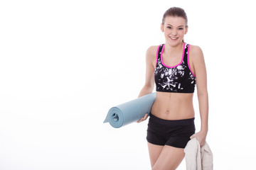 Healthy girl with yoga mattress and towels
