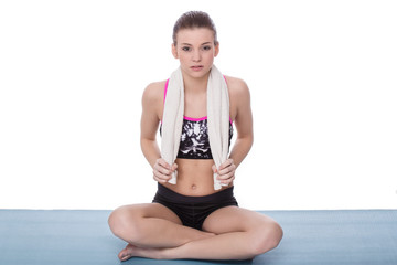 girl sitting on the yoga mattress with towels