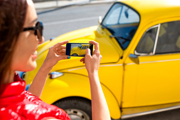 Woman photographing old yellow car