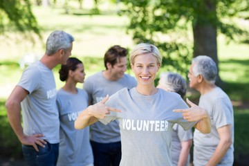 Happy volunteer blonde smiling at the camera