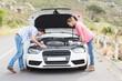Leinwanddruck Bild - Couple after a car breakdown