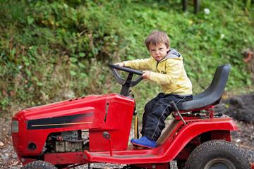 Adorable little boy, pretending to ride a lawn mower
