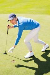 Female golfer picking up golf ball
