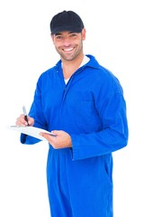 Handyman in blue overall writing on clipboard