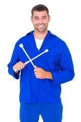 Smiling male mechanic holding lug wrench