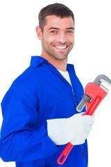 Smiling male mechanic holding monkey wrench
