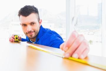 Handyman measuring wood board