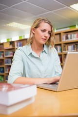 Pretty student studying in the library with laptop