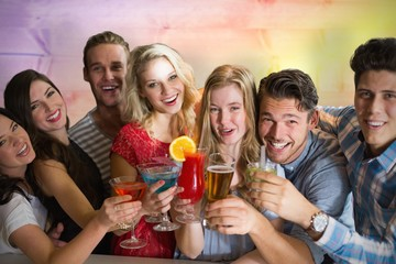 Composite image of friends drinking cocktails