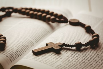 Open bible and wooden rosary beads
