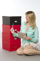Female office worker checking and stacking file boxes