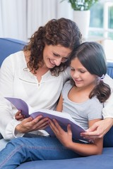 Happy mother and daughter sitting on the couch and reading book