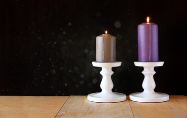 image of Burning candle on wooden table and black textured backg