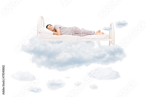 Young man sleeping on a comfortable bed in clouds