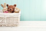 Stuffed animal toys in a basket on the floor. Turquoise wainscot