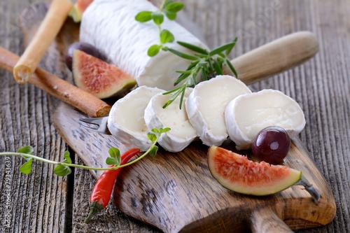 Staande foto Zuivelproducten Ziegenkäserolle mit Feigen und Grissini
