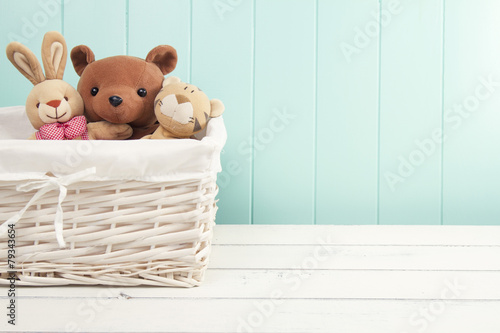 Retro Stuffed animal toys in a basket on the floor. Turquoise wainscot