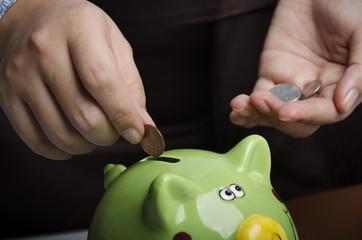 Closeup of saving US coins into piggy bank
