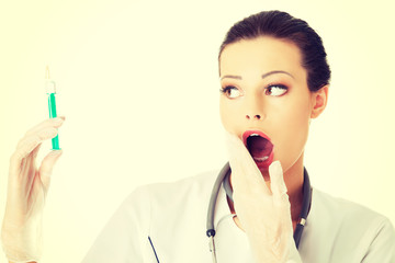 Shocked female doctor with a syringe.