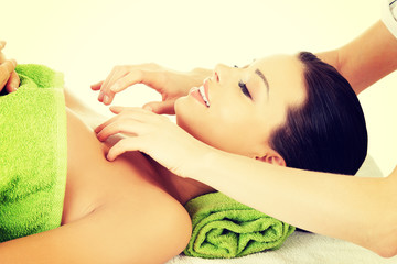 Relaxed woman enjoy receiving face massage.