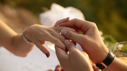 guy wears a ring on the finger of a girl