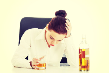 Businesswoman in depression drinking alcohol.