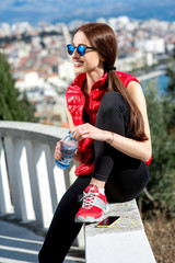 Sporty woman on the park alley with city view