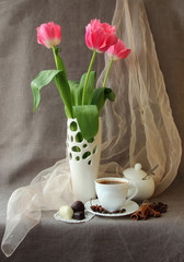 Pink tulips in a vase and cup of coffee..