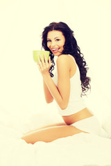 Beautiful woman drinking hot drink in bed.