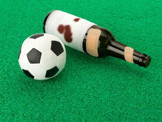 Fussball mit blutiger Bierflasche auf Kunstrasen