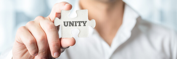 Businessman Showing Puzzle Piece with Unity Text