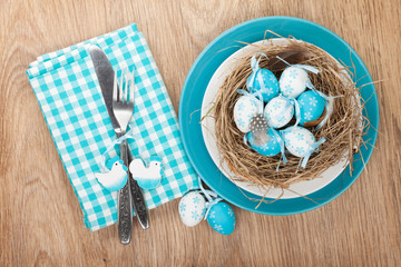Easter eggs nest on plate over wooden background