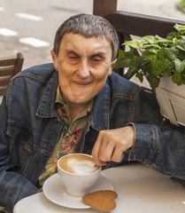 Disabled man with cerebral palsy sitting at cafe.