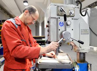 Arbeiter bedient Bohrmaschine im stahlbau