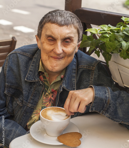 Disabled man with cerebral palsy sitting at cafe. - 79348409