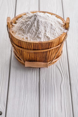 vintage wooden buclet with white natural flour on boards food an