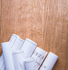 stack of white rolled up blueprints on wooden board with copyspa
