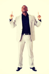 Handsome businessman pointing up.