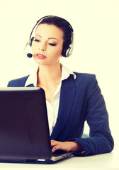 Support phone operator in headset with laptop.