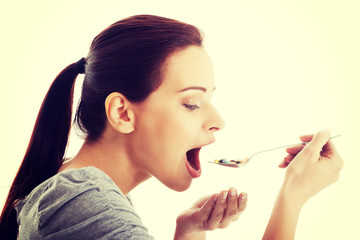 Woman eating pills on spoon.