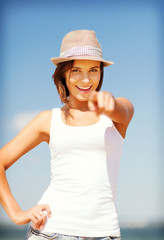 girl in hat pointing at you on the beach