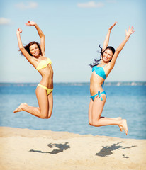 girls in bikini jumping on the beach