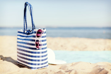 straw hat, sunglasses and bag lying in the sand