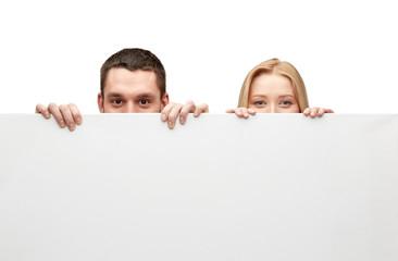 happy couple hiding behind big white blank board