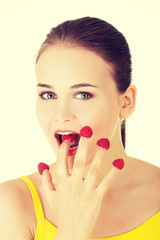 Woman with raspberries on her fingers.