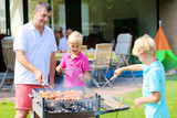 Father and sons grilling meat in the garden
