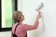 Female worker painting wall using paintroller, home renovation