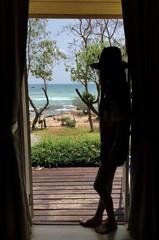 shadow of girl at the door looking to ocean.