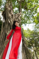 Woman in Red and White Dress Leaning at Tall Tree