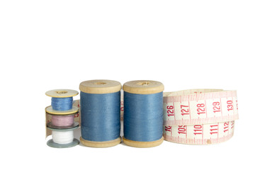 spools of thread with a ruler isolated over white